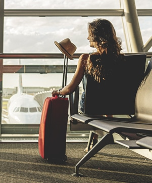 Woman sitting with suitcase in airport terminal