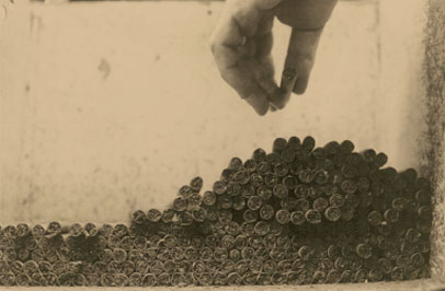 Sepia-toned photo of hand reaching for pile of cigars