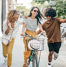Woman riding bicycle with two friends